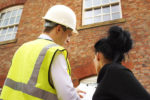 building survey being conducted with a man in high vis and hard hat