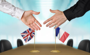 English and french flags with hands from each side about to shake