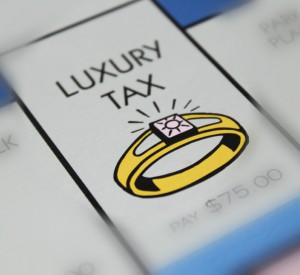 luxury tax text with a gold ring on a monopoly board