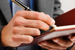 Businessman writing on his agenda