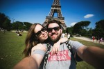 Romantic couple making selfie in front of Eiffel Tower while traveling in Paris, France. Happy smiling students enjoy  vacation in Europe.