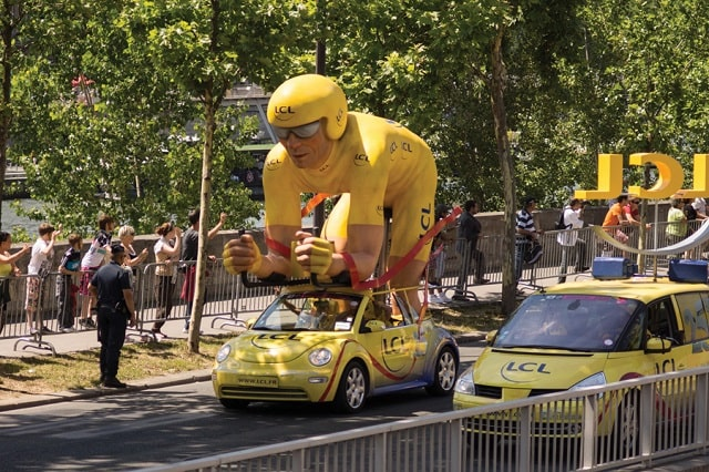 Sponsor vehicles are a sure sign that the peloton is approaching