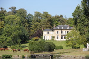French country house with a lake and horses