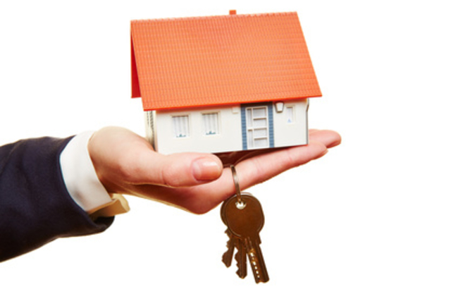 A hand holding a house with keys as representation of buying property in France
