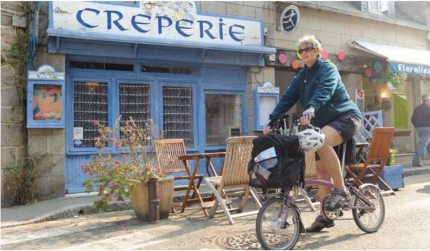 Woman on bike in front of a creperie in Brittany, France