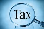 The word tax magnified in a magnifying glass