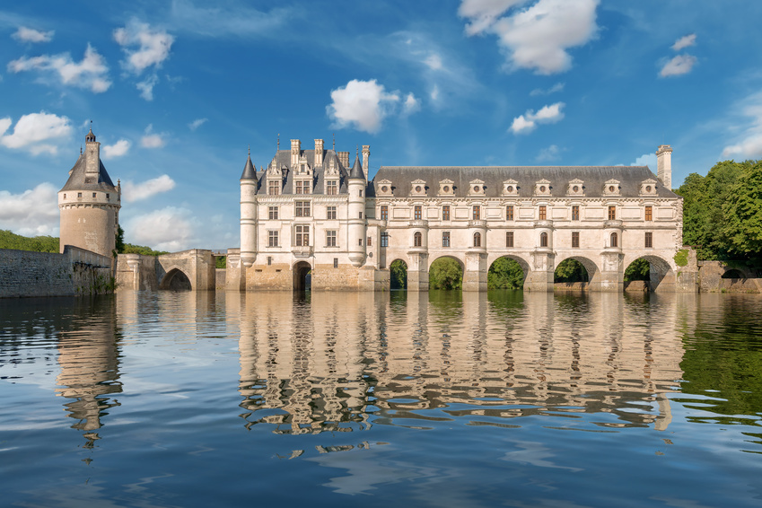 Chenonceau castle, built over the Cher river , Loire Valley,France, view from the river, on gradient blue cloudy sky background.