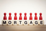 Mortgage concept: Red pawns on the word mortgage spelled by toy dice
