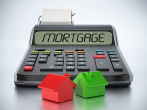 Mortgage written on a calculator with green and red model houses