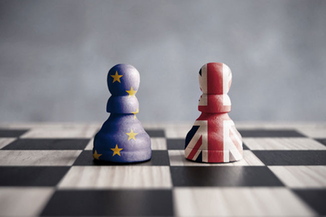 Chess pieces one painted as the European flag colours and one as the British flag colours