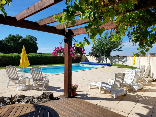 the back yard of a property in france it features a spacious patio and large swimming pool
