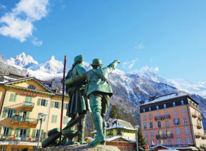 Statues in a ski village looking at the alps