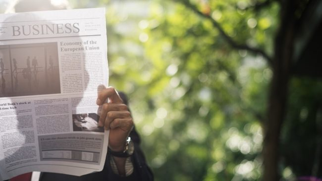 man looking at newspaper on business