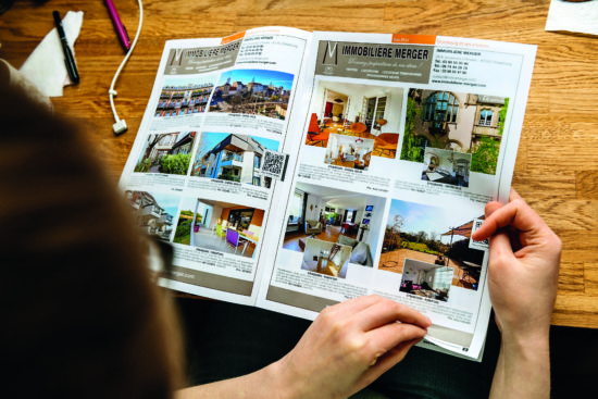Someone looking through property in the french entree magazine
