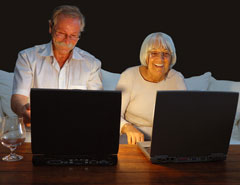 Older couple sat at laptops looking at readers advice for buying property in France