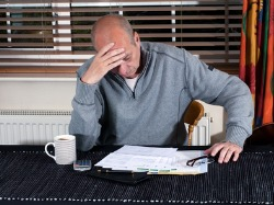 The burden of debt taking its toll on a gentleman at a table looking at paperwork