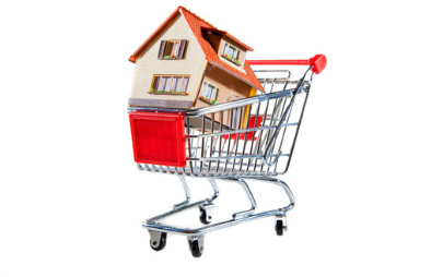 Model house in shopping trolley to represent property shopping cart